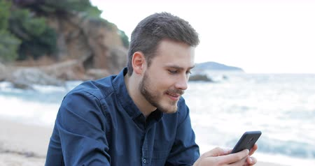 отменить : Disappointed man receiving wrong smart phone message on the beach