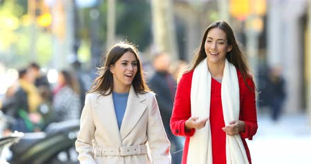 looking towards : Front view portrait of two happy friends talking and walking towards camera in the street Stock Footage