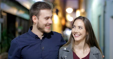 gives you : Front view portrait of a happy couple walking towards camera and talking in the night in the street