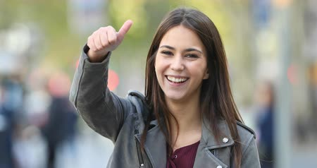потребитель : Happy teen gesturing thumbs up looking at camera in the street