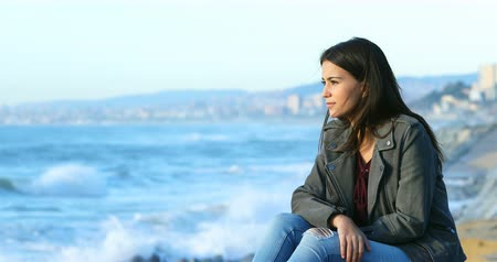 nadzieja : Relaxed teenage girl looking at horizon on the beach with the sea in the background