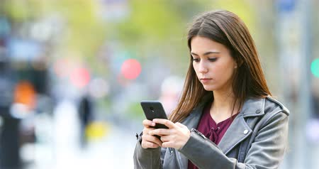 ciddi : Serious teenage girl texting on smart phone outdoors in the street Stok Video