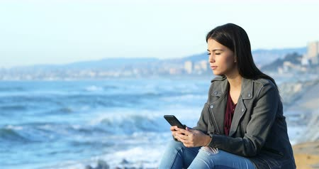 átlagos : Relaxed teen checking smart phone and looking at horizon on the beach