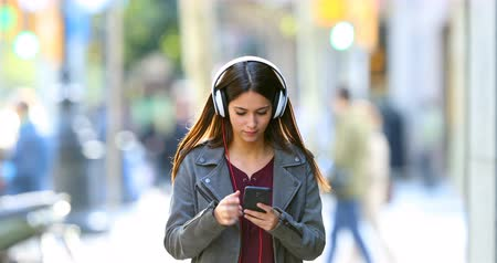 stahování : Front view of a happy teen listening to music dancing in the street