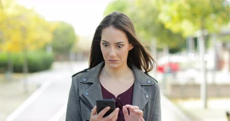 содержание : Front view of a perplexed woman walking checking smart phone content and then stops looking at camera in a park