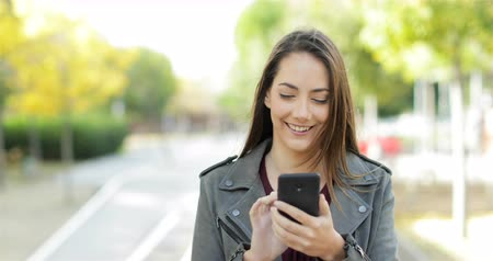conectado : Front view of a happy woman walking and browsing on smart phone in a park
