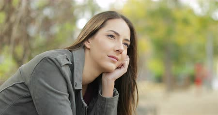 özlem : Portrait of a serious pensive woman looking away sitting in a park