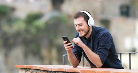 chill out : Happy man listening to music from smart phone in a rural apartment balcony and looks away