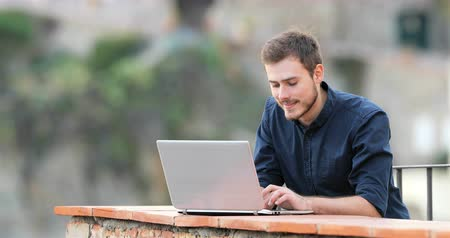 kurs : Happy man typing on a laptop in a balcony of a rural apartment
