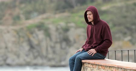 faint : Sad teen contemplating ocean complaining from a terrace in a coast town
