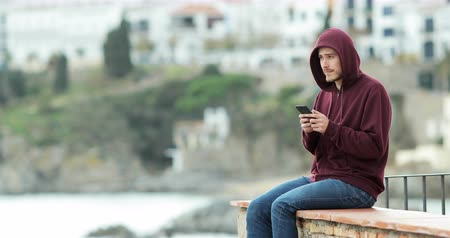 özlem : Serious teen texting on the phone and looking away to the horizon sitting on a ledge on a beach town