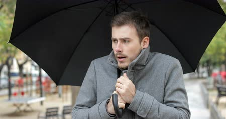 annoying : Front view portrait of an angry man getting cold walking towards camera under an umbrella in the rainy winter day