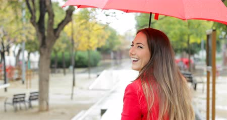 esteem : Back view of a happy woman walking smiling at camera holding a red umbrella under the rain