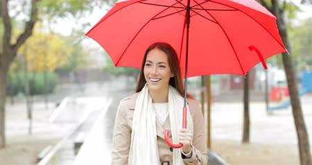 esteem : Front view portrait of a happy woman walking holding a red umbrella under the rain in winter Stock Footage