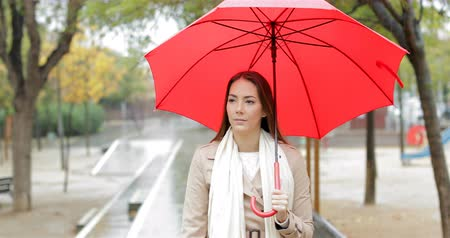esteem : Front view portrait of a serious woman walking holding a red umbrella under the rain in a park