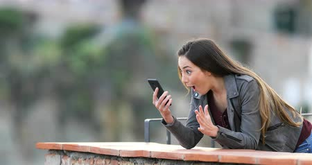 vendég : Surprised woman finding smart phone content in a rural apartment balcony Stock mozgókép