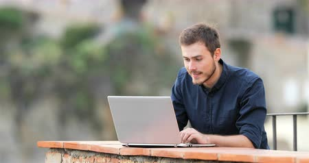 self promotion : Excited man finding online content on a laptop in a rural apartment terrace