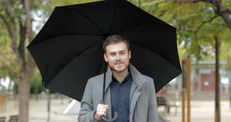 esteem : Front view portrait of a happy man walking in a park under the rain holding an umbrella looking at you in winter Stock Footage