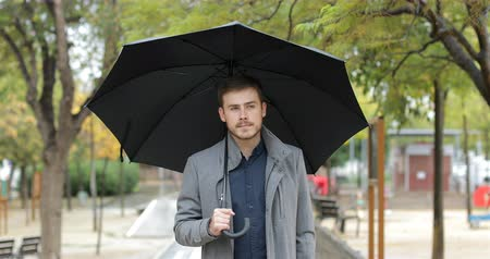 esteem : Front view portrait of a serious man walking towards camera holding an umbrella under the rain in winter in a park