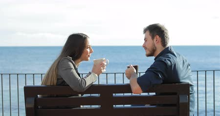 gives you : Side view portrait of a happy couple talking and drinking coffee sitting on a bench on the beach Stock Footage