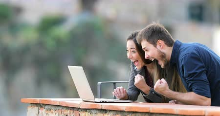 поощрение : Excited couple finding online content in a laptop in a rural apartment balcony