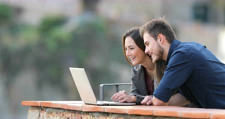 gives : Happy couple browsing laptop in a rural apartment balcony