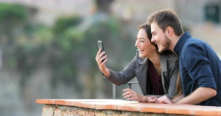 tárcsázás : Happy couple having a video call with a smart phone in a rural apartment terrace