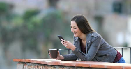 átlagos : Happy woman drinking coffee and using a smart phone in a rural apartment balcony