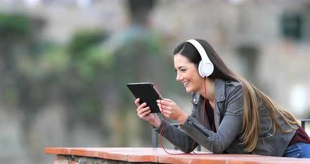 mobile music : Happy woman watching and listening to music on a tablet in a rural apartment terrace
