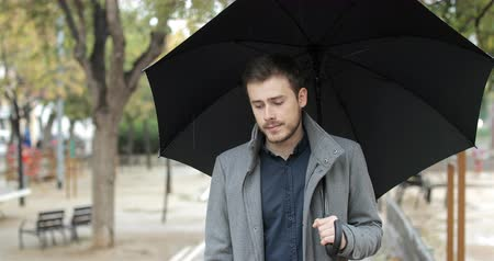 cheated : Front view of a sad man walking alone in a rainy day of winter holding an umbrella in a park