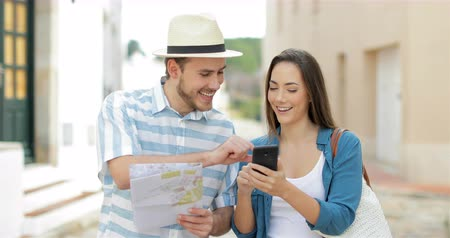 adult woman : Front view of a couple of happy tourists walking towards camera and booking Stock Footage