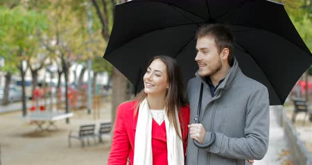 amantes : Front view of a happy couple walking towards camera and pointing away under the rain in winter