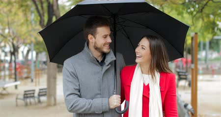 andar : Front view of a happy couple walking and talking under the rain in winter Vídeos
