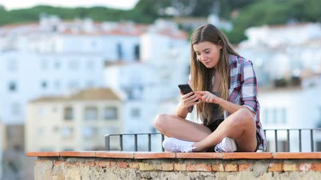 grants : Excited teen lying on a smart phone sitting on a ledge on vacation