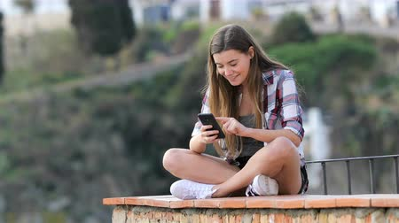 gemiddeld : Happy teenage girl browsing smart phone content sitting on a ledge in a coast town on vacation Stockvideo