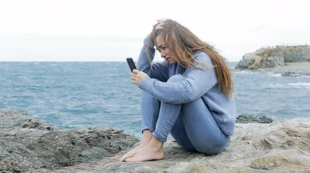 cheated : Sad teen complaining after reading smart phone message on a rock on the beach Stock Footage