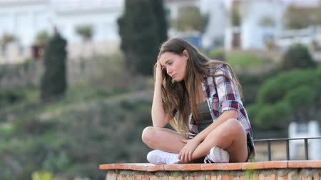cheated : Sad teenage girl complaining sitting on a ledge in a town on vacation Stock Footage