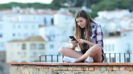 téma : Surprised teenage girl finding online content on a smart phone sitting on a ledge on vacation