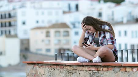 faint : Sad teenage girl crying after reading text on a smart phone sitting on a ledge on vacation
