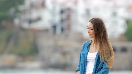 faint : Melancholic woman looking away outdoors in a coast town