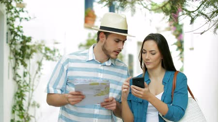 бронирование : Couple of tourists booking online on the phone and finding best in the street