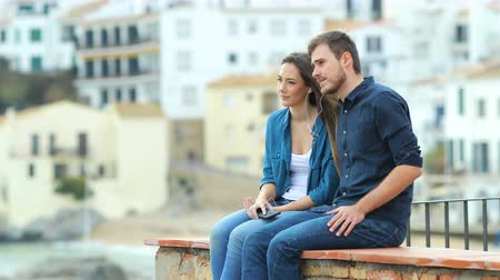 breathing fresh air : Serious couple sharing music and breathing outdoors sitting on a ledge on vacation