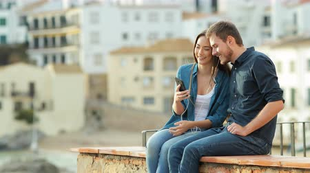 gives you : Happy couple listening to music from a smart phone sharing earphones sitting on a ledge in a coast town at sunset