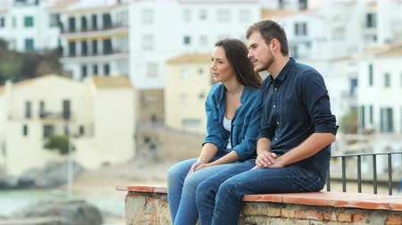 rustik : Serious couple of friends talking looking away on a ledge on vacation in a coast town