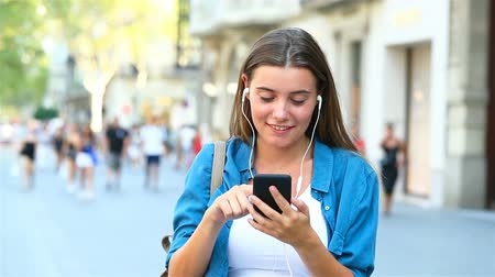 наушники : Front view of a girl choosing and listening to music from smart phone outdoor in the street