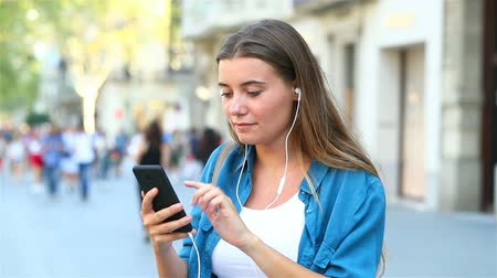tárcsázás : Happy girl having a video call with smart phone and earphones in the street Stock mozgókép