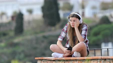 faint : Sad teen listening to music on vacation sitting on a ledge in a town