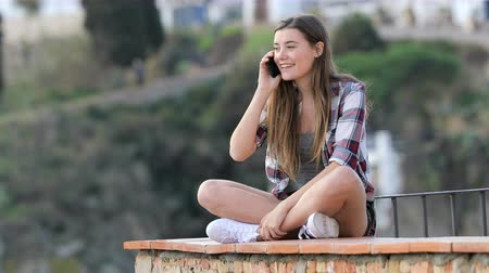 žádost : Happy teenage girl calling on phone on a ledge in a town on vacation Dostupné videozáznamy