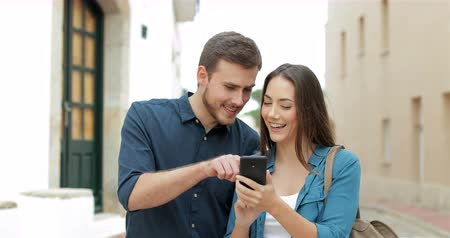 gives you : Happy couple walking towards camera browsing cellphone content in the street