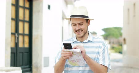 бронирование : Happy tourist man browsing smart phone content walking in the street on vacation